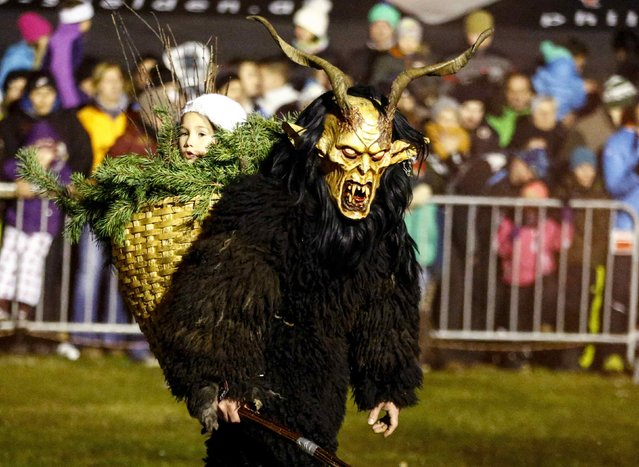 A man dressed in a tradtional Perchten costume and mask performs during a Perchten festival in the western Austrian village of Huben November 22, 2014. Each year in November and January people in the western Austria regions dress up in Perchten (also known in some regions as Krampus or Tuifl) costumes and parade through the streets to perform a 1,500 year-old pagan ritual to disperse the ghosts of winter. (Photo by Dominic Ebenbichler/Reuters)