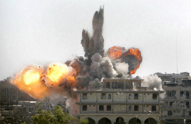 A building explodes as the first bomb drops during a U.S. aerial assault on insurgent targets in Najaf, Iraq, on August 19, 2004. (Photo by Jim MacMillan/AP Photo/The Atlantic)