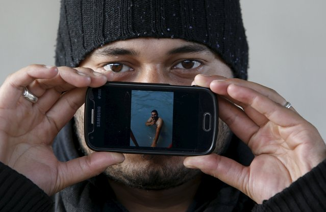Migrant Hammad from Damascus, Syria, shows a picture of him swimming in a pool as he waits to cross the Slovenia-Austria border in Sentilj, Slovenia October 25, 2015. (Photo by Srdjan Zivulovic/Reuters)
