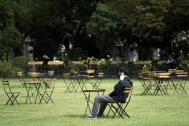 A man pulling off a protective mask rests at an open air cafe Monday, October 12, 2020, in Tokyo. The Japanese capital confirmed more than 70 coronavirus cases on Monday. (Photo by Eugene Hoshiko/AP Photo)
