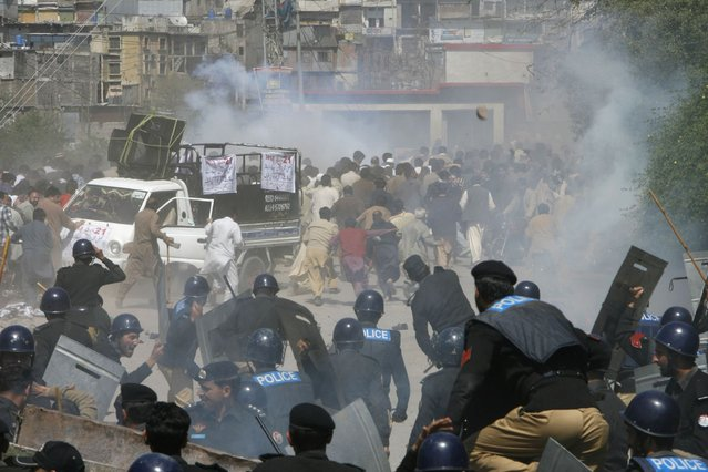 Riot police officers run towards towards protesters during a demonstration against power outage in Muzffarabad, capital of Pakistan-administrated Kashmir March 21, 2013. People protesting against power outage in Muzaffarabad turned violent on Thursday. Around 50 people, including a police official, sustained minor injuries when the protesters pelted stones at the police and burnt a police bus, local media reported. (Photo by Amiruddin Mughal/Reuters)