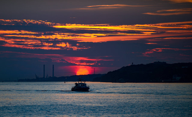 The sunset is pictured over the river Elbe in Hamburg, northern Germany, on August 28, 2017. (Photo by Axel Heimken/AFP Photo/DPA)