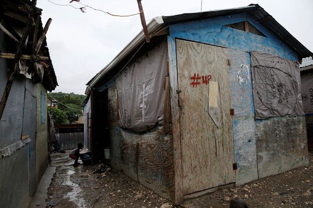 A child carries a plastic container next to his house in a camp for displaced people while Hurricane Matthew approaches in Port-au-Prince, Haiti October 3, 2016. (Photo by Carlos Garcia Rawlins/Reuters)
