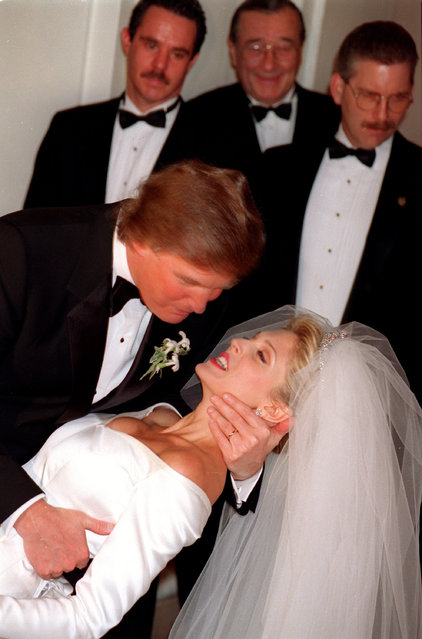 Donald Trump, left, sweeps his bride, Marla, off her feet to kiss her in front of photographers after their wedding ceremony at New York's Plaza Hotel, December 20, 1992.  (Photo by Kathy Willens/AP Photo)