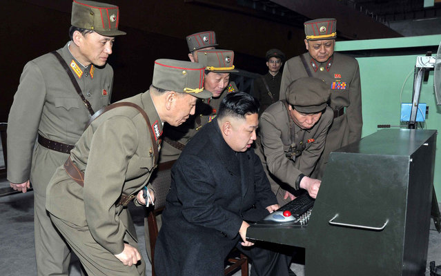 North Korean leader Kim Jong Un (center) looks at the latest combat and technical equipment, made by unit 1501 of the Korean People's Army, during his visit to the unit, on March 24, 2013. (Photo by Reuters/KCNA)