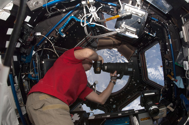 Canadian Space Agency astronaut Chris Hadfield uses a camera to photograph the Earth from a window in the Cupola of the ISS, on January 7, 2013. (Photo by NASA/The Atlantic)