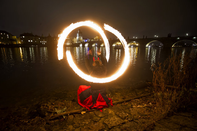A young woman dressed as a devil waves with fire on the bank of Vltava river near the Charles Bridge on December 5, 2014 in Prague, Czech Republic. Devils, angels and St. Nicholas were out in full force, roaming the streets to reward children who have been good and admonish those who have not in the annual Czech tradition known as Svaty Mikulas. (Photo by Matej Divizna/Getty Images)