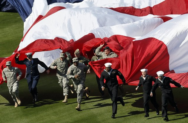 Members of the U.S. military run a large flag onto the field before the Philadelphia Phillies home opener against the Kansas City Royals in their MLB Interleague baseball game in Philadelphia, Pennsylvania, April 5, 2013. (Photo by Tim Shaffer/Reuters)
