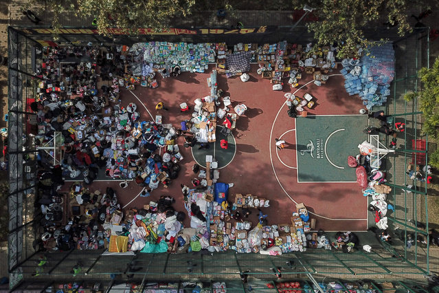 This aerial view shows and food and clothing aid sent by supporters of Goztepe Football Club to affected residents, laid out on a basketball court in Izmir on November 3, 2020, after the Aegean port city was struck by a 7.0-magnitude earthquake. Rescue workers were searching eight buildings in Izmir despite dwindling hope for survivors, as the death toll of a powerful magnitude earthquake which hit western Turkey rose to 69. The 7.0-magnitude quake has also injured 896 in Turkey, the Turkish emergency authority AFAD said, after striking on October 30, afternoon near the west coast town of Seferihisar in Izmir province. (Photo by Ozan Kose/AFP Photo)