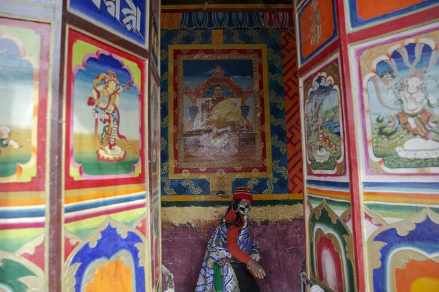 An ethnic Tibetan woman walks under the picture of Khenpo Jigme Phuntsok behind prayer wheels at the Larung Wuming Buddhist Institute, located some 3700 to 4000 metres above the sea level in remote Sertar county, Garze Tibetan Autonomous Prefecture, Sichuan province, China October 30, 2015. (Photo by Damir Sagolj/Reuters)
