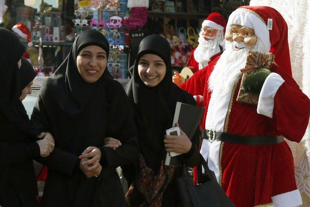 Veiled women walk past Santa Claus statues in Nabatiyeh, in south Lebanon December 14, 2014. (Photo by Ali Hashisho/Reuters)