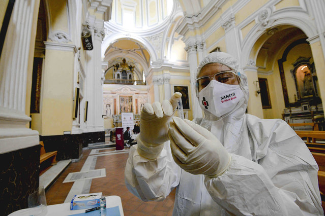 """A medical operator prepares to perform COVID-19 test swabs in the Church of San Severo Outside the Walls, in the heart of Naples, Italy, Wednesday, November 18, 2020. An initiative of """"Sanita' Diritti Salute"""" association and the San Gennaro Foundation, aimed at helping those who cannot afford the cost of a private test, also allows, in the best tradition of Naples, those who want to pay 18 euros for a """"suspended swab"""", to be taken by somebody else, exactly as it happens for the famous Neapolitan """"suspended coffee"""". (Photo by Alessandro Pone/LaPresse via AP Photo)"""