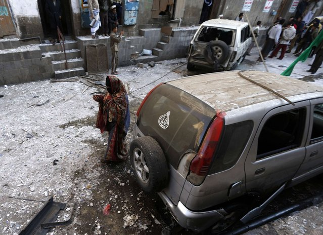 A woman walks at the site of a bomb explosion in Sanaa December 23, 2014. (Photo by Khaled Abdullah/Reuters)