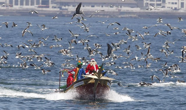 Ruben Torres, dressed in a Santa Claus outfit, and fishermen stand on a boat on Christmas Eve along the coast of Valparaiso city, northwest of Santiago, December 24, 2014. Every year, fishermen in Valparaiso organize a Santa Claus boat trip as people wait on the shore to receive their Christmas presents and well-wishes. (Photo by Rodrigo Garrido/Reuters)