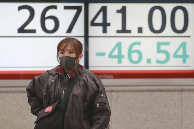 A woman walks by an electronic stock board of a securities firm in Tokyo, Wednesday, December 2, 2020. Asian markets are mixed after the U.S. benchmark S&P 500 set another record. (Photo by Koji Sasahara/AP Photo)