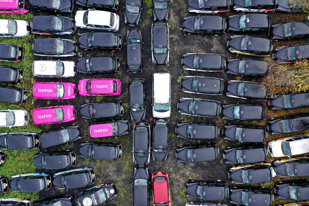 An aerial view shows black London taxi cabs parked up in a field in Epping, north-east of London on November 19, 2020. Picking up a fare has become so hard for London's legendary black cabs that many taxis are being mothballed. Some taxi drivers who hire their cabs have returned them to fleet companies, which are then forced to store the vehicles in fields around the city. (Photo by Will Edwards/AFP Photo)