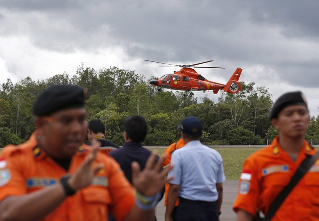 An Indonesian Search and Rescue helicopter carrying the bodies of two AirAsia passengers recovered from the sea prepares to land at the airport in Pangkalan Bun, Central Kalimantan, December 31, 2014. (Photo by Darren Whiteside/Reuters)