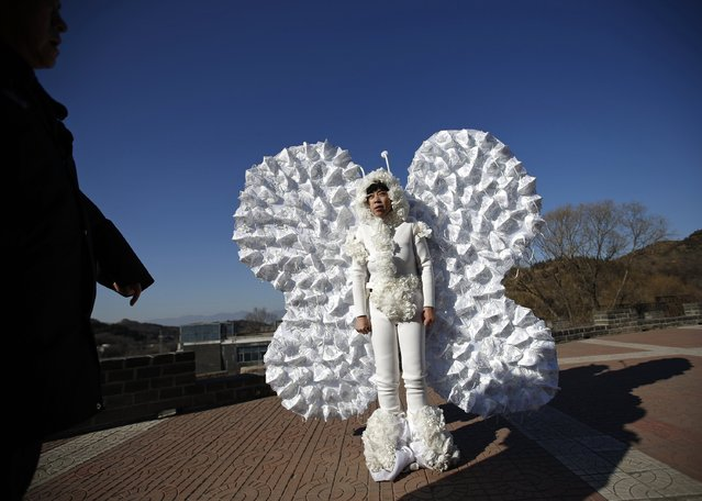 Chinese artist Kong Ning wearing a costume symbolizing a butterfly, which is decorated with 365 masks on its wings to represent the number of days in a year, reacts as she is stopped by an official from a management office of Badaling section of the Great Wall during her performance art on the outskirts of Beijing January 1, 2015. (Photo by Kim Kyung-Hoon/Reuters)