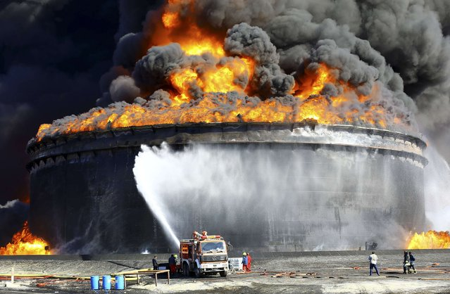 Firefighters work to put out the fire of a storage oil tank at the port of Es Sider in Ras Lanuf December 29, 2014. Oil tanks at Es Sider have been on fire for days after a rocket hit one of them, destroying more than two days of Libyan production, officials said on Sunday. Libya has appealed to Italy, Germany and the United States to send firefighters. (Photo by Reuters/Stringer)