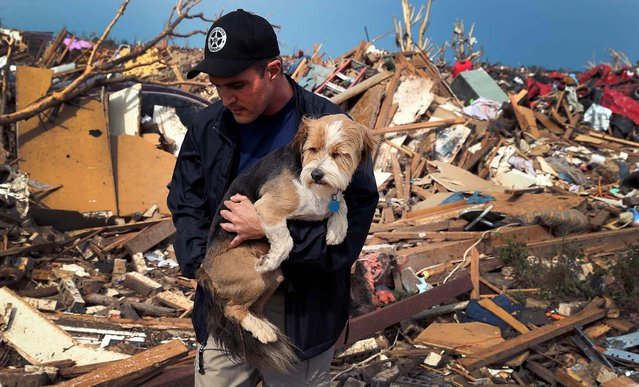On Tuesday, Sean Xuereb recovers a dog from the rubble of a home in Moore. (Photo by Scott Olson/Getty Images)