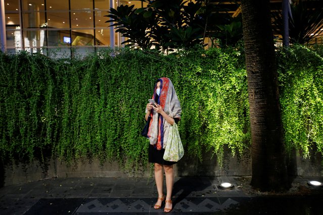 A woman wearing a protective mask stands as she waits for the bus at the sidewalk, after Indonesia confirmed its first cases of coronavirus, in Jakarta, Indonesia, March 4, 2020. (Photo by Willy Kurniawan/Reuters)
