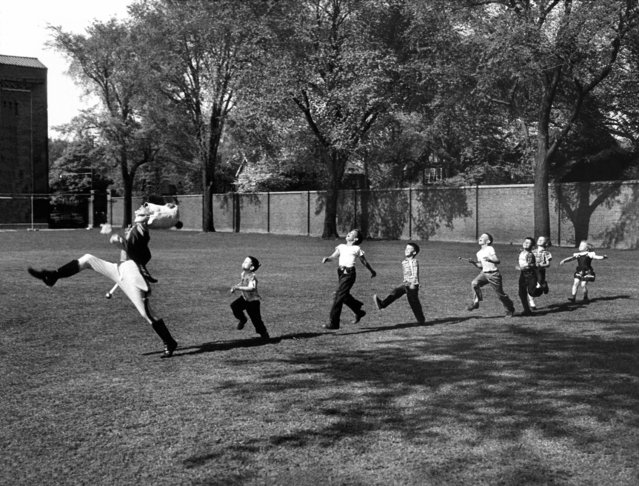 Uniformed drum major for the University of Michigan  marching band practicing his high-kicking prance as he leads a line of seven admiring children who are all trying to imitate his flamboyant technique while marching across the campus lawn, 1950. (Photo by Alfred Eisenstaedt/Time & Life Pictures)