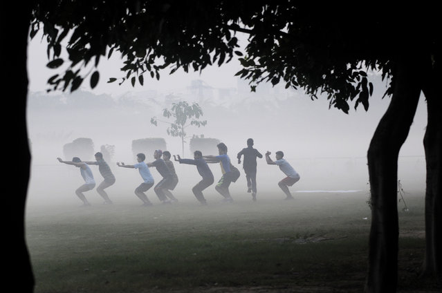 People exercising in a park amidst fog on November 23, 2015 in Noida, India. It was a misty morning here with the minimum temperature recorded at 11 degrees Celsius. (Photo Sunil Ghosh/Hindustan Times via Getty Images)