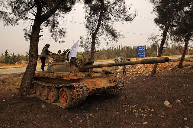 Rebel fighters stand on a tank in Dahiyat al-Assad, west Aleppo city, Syria October 28, 2016. (Photo by Ammar Abdullah/Reuters)