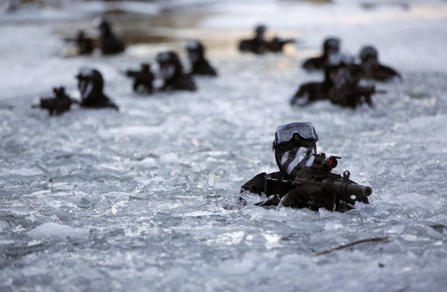 Members of the South Korean Special Warfare Forces take their positions in frozen waters during a winter exercise in Pyeongchang January 8, 2015. (Photo by Kim Hong-Ji/Reuters)