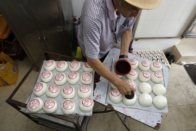 """A man stamps the sign featuring the Chinese character """"Peace"""" on buns for sale on the outlying Cheung Chau island in Hong Kong to celebrate the Bun Festival Tuesday, May 22, 2018. Thousands of people flocked to an outlying island in Hong Kong on Tuesday to celebrate a local bun festival despite recording-breaking heat. A parade featured children dressed as deities floated on poles. Later, contestants in a bun-scrambling competition raced up a 14-meter (46-foot) bamboo tower to snatch as many plastic buns as possible. Buns higher up the pole are worth more points. One of Hong Kong's oldest and most colorful festivals started about a century ago after a deadly plague devastated the outlying island of Cheung Chau. Residents built an altar in front of the Pak Tai temple imploring the deities for help and used white steamed buns as offerings to drive away the evil spirits, according to tradition. The bun-snatching contest was canceled after a bun tower collapsed in 1978, injuring 100 people. The tradition was revived in 2005 as part of an annual """"bun festival"""". As added safety measures this year, workers built a sturdier tower and bun snatchers received mountaineering training. (Photo by Kin Cheung/AP Photo)"""