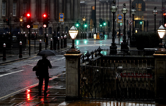 A man with an umbrella walks through a street in the financial area of London, Wednesday, January 13, 2021 during England's third national lockdown to curb the spread of coronavirus. (Photo by Alastair Grant/AP Photo)