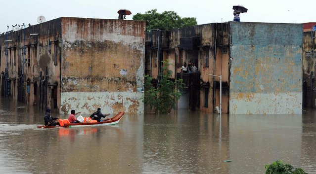Rescue workers carry food in a boat to distribute to people trapped in a flooded residential area in Chennai, in the southern Indian state of Tamil Nadu, Wednesday, December 2, 2015. Weeks of torrential rains have forced the airport in the state capital Chennai to close and have cut off several roads and highways, leaving tens of thousands of people stranded in their homes, government officials said Wednesday. (Photo by AP Photo)