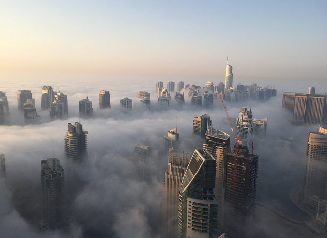 A general view shows the part of the skyline of Dubai covered in an early morning fog on October 5, 2015. (Photo by Rene Slama/AFP Photo)