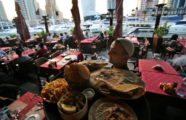 In this April 1, 2015 photo, a waiter carries a tray of traditional Arabic food at a restaurant by the water canal at the Marina district, in Dubai, United Arab Emirates. Surrounding the Marina's canal is an oasis of trendy restaurants and bars that serve an array of fusion-style cuisines that reflect the myriad of cultures and people drawn to Dubai, a modern city-state where foreigners far outnumber the locals. (Photo by Kamran Jebreili/AP Photo)
