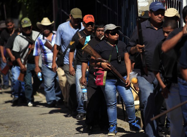 Members of the Community Police of the FUSDEG (United Front for the Security and Development of the State of Guerrero) take part in a march to mark the first anniversary of the force's operations in Ocotito, January 23, 2015. (Photo by Jorge Dan Lopez/Reuters)