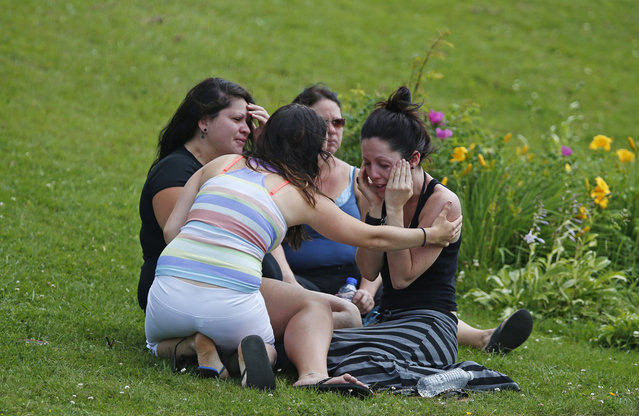 A woman comforts her friend while they sit on the grass at the Polyvalente Montignac, a school sheltering people who were forced to leave their houses after the explosion, in Lac-Megantic, on July 7, 2013. (Photo by Mathieu Belanger/Reuters)