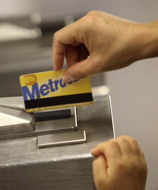 A subway rider swipes a MetroCard through the turnstiles in New York, July 28, 2010. New York's transit agency is proposing fare increases of more than 16 percent for monthly subway and bus passes and 9 percent hikes on suburban trains, another blow to commuters still getting used to service cuts last month that eliminated some subway and bus routes. (Photo by Seth Wenig/AP Photo)