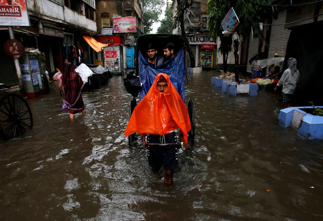 A rickshaw puller transports passengers through a water-logged street after heavy rain in Kolkata, India on June 26, 2018. (Photo by Rupak De Chowdhuri/Reuters)