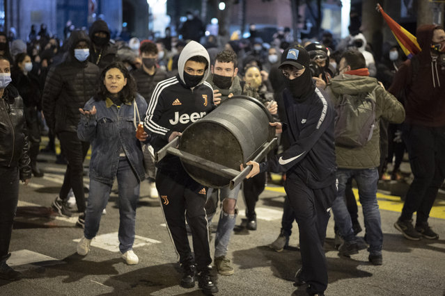 Demonstrators carry a rubbish bin to throw it agains police officers protecting a national police station during clashes following a protest condemning the arrest of rap singer Pablo Hasél in Barcelona, Spain, Sunday, February 21, 2021. Protests in support of a jailed rapper turned violent for a sixth consecutive night in Barcelona on Sunday with clashes between police and groups of mostly angry youths in the center of the Spanish city. (Photo by Emilio Morenatti/AP Photo)