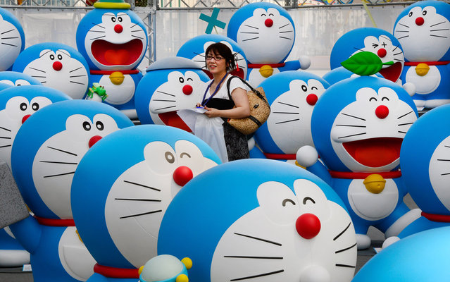 A journalist walks amid life-size figures of Doraemon on the roof of the Tokyo Tower Foot Town during the press preview of the Fujiko F Fujio Exhibition on July 18, 2013. The exhibition will be held from July 19 to October 6. (Photo by Toru Yamanaka/AFP Photo)