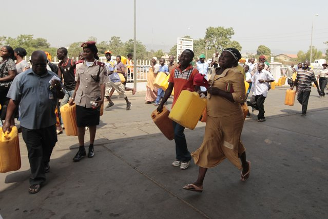 "People run toward kerosene cooking fuel pumps during the launch of the ""kero correct"" scheme at a Nigerian National Petroleum Corporation (NNPC) mega petrol station in Abuja January 23, 2015. The NNPC commenced sale of kerosene cooking fuel, which a majority of Nigerians depend on for cooking, at a reduced pump price of $0.27 per litre nationwide at all NNPC outlets. (Photo by Afolabi Sotunde/Reuters)"