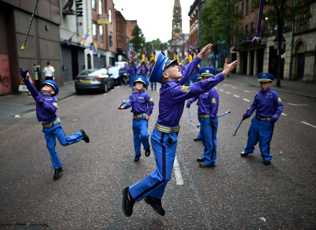 Young band members throw their batons in the air as the annual 12th of July Orange march and demonstration taking place on July 12, 2018 in Belfast, Northern Ireland. The marches across the province celebrate King William of Orange's victory over the Catholic King James at the Battle of the Boyne in 1690. (Photo by Charles McQuillan/Getty Images)