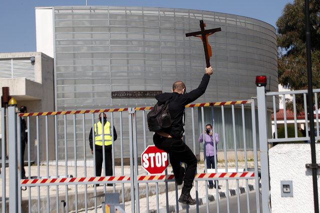 """A protestor holding a cross climbs a gate outside Cyprus' national broadcasting building, during a protest, in capital Nicosia, Cyprus, Saturday, March 6, 2021. The Orthodox Church of Cyprus is calling for the withdrawal of the country's controversial entry into this year's Eurovision song context titled """"El Diablo"""", charging that the song makes an international mockery of country's moral foundations by advocating """"our surrender to the devil and promoting his worship"""". (Photo by Petros Karadjias/AP Photo)"""