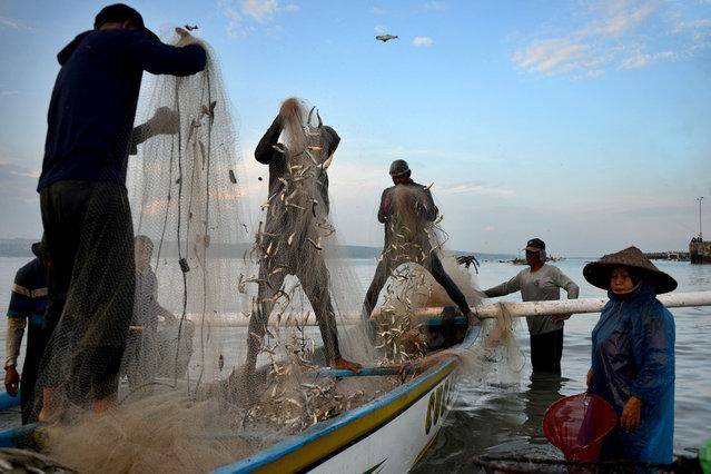 Fishermen check their nets after returning to the Kedonganan beach near Denpasar, on Indonesia resort island of Bali on February 26, 2021. (Photo by Sonny Tumbelaka/AFP Photo)