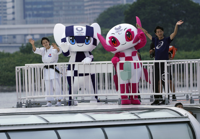 """Tokyo 2020 Olympic mascot """"Miraitowa"""" and Paralympic mascot """"Someity"""" wave as they board a boat during their water parade with town's landmark """"Rainbow Bridge"""" as back ground in Tokyo Sunday, July 22, 2018. The official mascots for the Tokyo 2020 Olympics and Paralympics were unveiled at a ceremony on Sunday. The two mascot designs were selected by elementary schoolchildren across Japan. (Photo by Eugene Hoshiko/AP Photo)"""