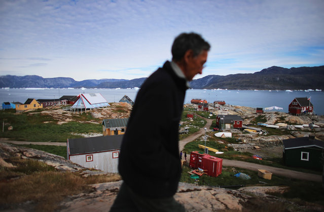 A person walks through the village of Qeqertaq, Greenland, on July 20, 2013. As Greenlanders adapt to the changing climate and go on with their lives, researchers from the National Science Foundation and other organizations are studying the phenomena of the melting glaciers and its long-term ramifications for the rest of the world. (Photo by Joe Raedle/Getty Images via The Atlantic)
