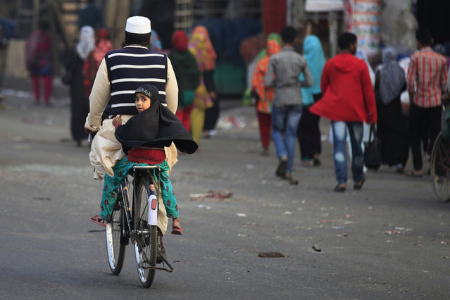 A Bangladeshi child travels on a bicycle with her guardian during the second day of 72 hours long strike called by the opposition Bangladesh Nationalist Party (BNP) led alliance in Dhaka, Bangladesh, Monday, February 2, 2015. (Photo by A. M. Ahad)/AP Photo