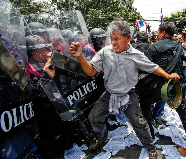 An anti-government protester fights  police  outside the parliament in Bangkok, on August 7, 2013. Thailand's parliament will debate a political amnesty bill that the protesters fear will allow the ex-premier Thaksin Shinawatra to return from exile without having to serve a jail sentence. (Photo by Athit Perawongmetha/Associated Press)