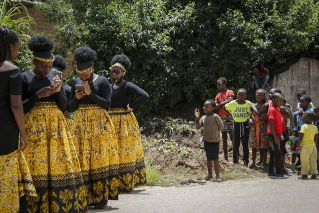 Children watch bridesmaids as they check their phones at a traditional marriage ceremony in the capital Harare, Zimbabwe Saturday, March 6, 2021. (Photo by Tsvangirayi Mukwazhi/AP Photo)