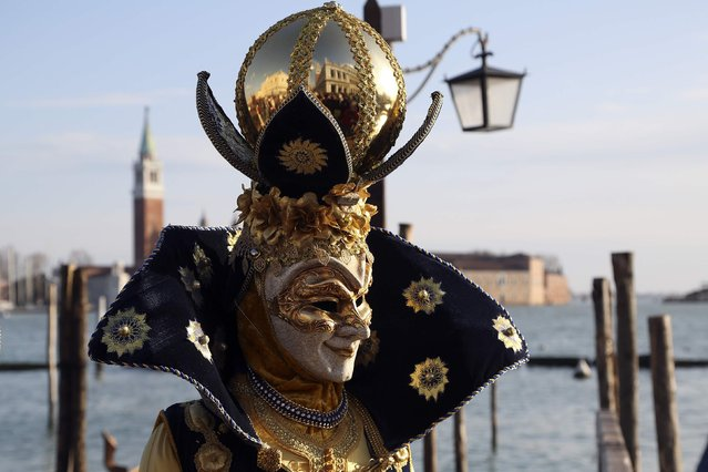 A masked reveller poses in front of St. Mark's Square during the Venice Carnival, February 7, 2015. (Photo by Stefano Rellandini/Reuters)